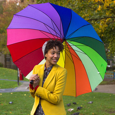 woman-in-park-with-rainbow-umbrella_web